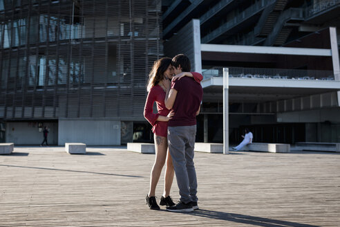 Affectionate young couple standing on city square - MAUF01451
