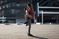 Young man lifting up happy girlfriend on city square - MAUF01454