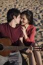 Affectionate couple with a guitar sitting on the beach - MAUF01463