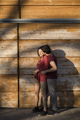 Happy affectionate young couple standing at wooden wall - MAUF01472