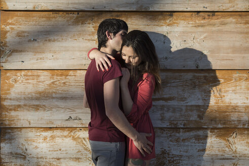 Affectionate young couple hugging and kissing at wooden wall - MAUF01475