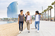 Spain, Barcelona, three friends walking on beach promenade - WPEF00649
