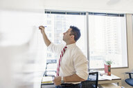 Business lawyer writing on whiteboard in office meeting - ISF16529