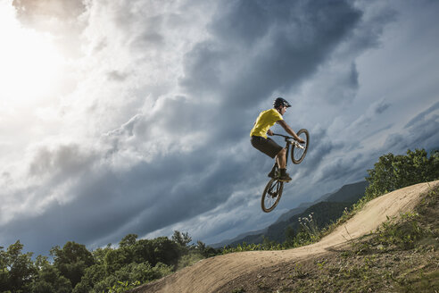 Young male mountain biker jumping mid air on rural pump track - ISF16592