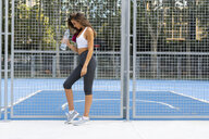 Sportive young woman standing at sports field holding water bottle - KKAF01149