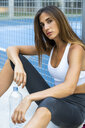Portrait of sportive young woman sitting at sports field with water bottle - KKAF01152