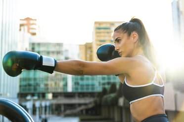 Sportive young woman boxing in the city - KKAF01158