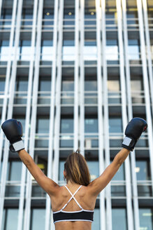 Sportive young woman with boxing gloves in the city raising her arms - KKAF01170