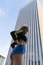 Attractive young woman standing in front of skyscraper in the city - KKAF01182