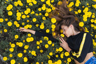 Attractive young woman lying in flower meadow - KKAF01185