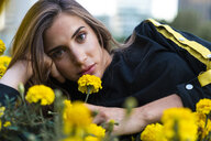 Portrait of attractive young woman lying in flower meadow - KKAF01188