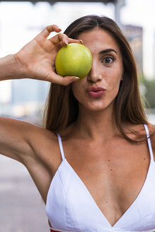 Portrait of attractive young woman wearing sports bra holding an apple - KKAF01197