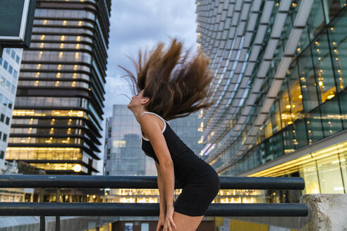 Carefree young woman wearing black dress in the city at dusk tossing her hair - KKAF01209