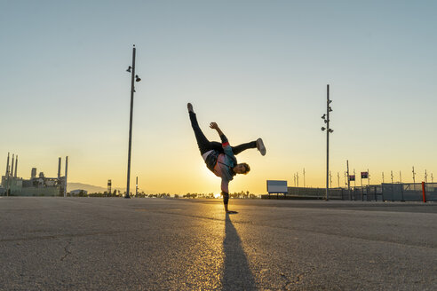 Acrobat doing handstand in the city at sunrise - AFVF00666