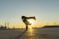 Acrobat doing handstand in the city at sunrise - AFVF00669