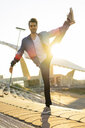 Man balancing on one leg, smiling - AFVF00678