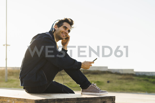 Man with headphones sitting on wood stack, using smartphone - AFVF00684