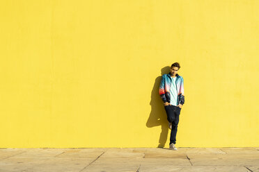 Man leaning against yellow wall with hands in pockets - AFVF00693