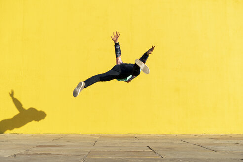 Acrobat jumping somersaults in front of yellow wall - AFVF00696