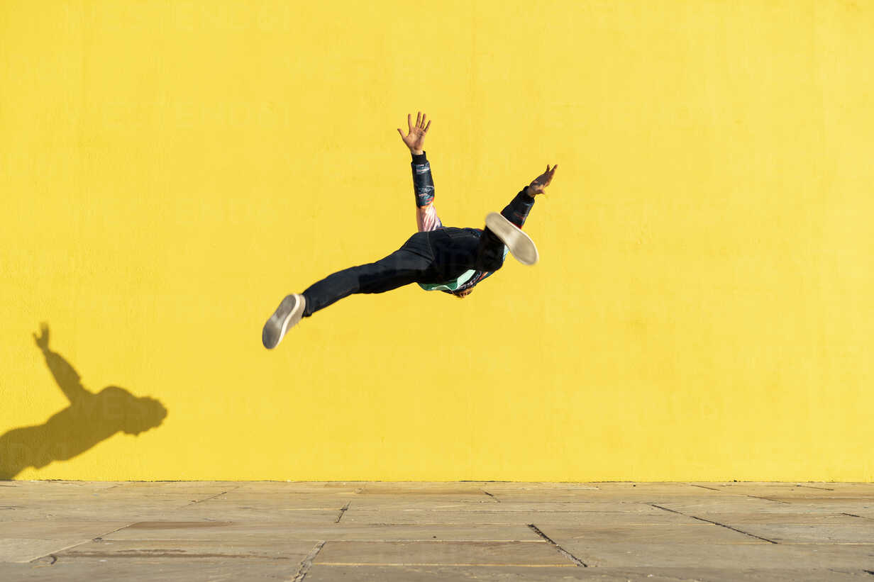Acrobat jumping somersaults in front of yellow wall - AFVF00696 - VITTA GALLERY/Westend61
