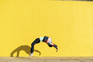 Acrobat jumping somersaults in front of yellow wall - AFVF00699