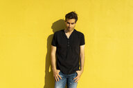 Man standing in front of yellow wall, portrait - AFVF00702