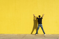 Man standing with hands on yellow wall, rear view - AFVF00705