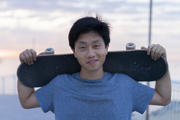 Young Chinese man with skateboard at the beach at sunrise - AFVF00714