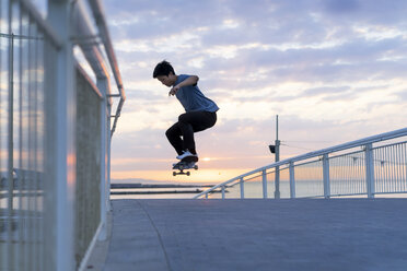 Young Chinese man skateboarding at sunsrise near the beach - AFVF00717