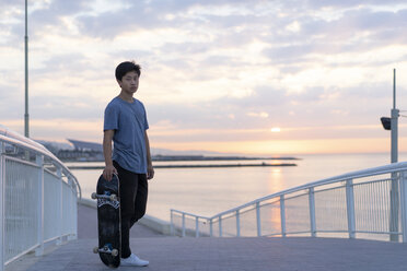 Young Chinese man with skateboard at the beach at sunrise - AFVF00720