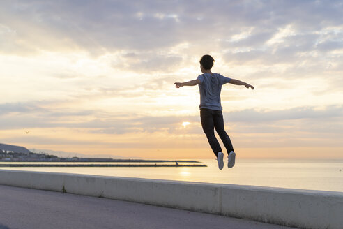 Young Chinese man jumping on wall at the beach - AFVF00726