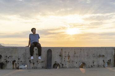 Young Chinese man sitting on wall at sunrise - AFVF00729