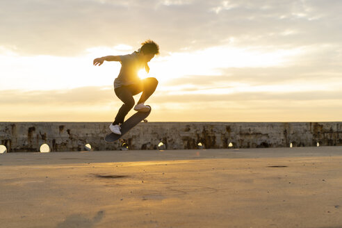 Young Chinese man skateboarding at sunsrise near the beach - AFVF00732