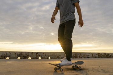 Young Chinese man skateboarding at sunsrise near the beach - AFVF00735