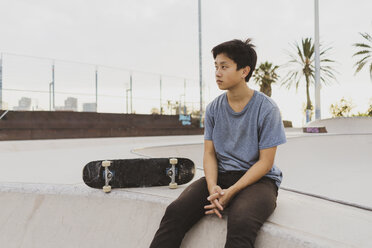 Young Chinese man sitting on wall of a skate park near the beach - AFVF00738