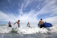 Group of male and female surfer friends wading into sea with surf boards - ISF16664