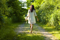 Rear view of young woman strolling barefoot along rural track, Delaware Canal State Park, New Hope, Pennsylvania, USA - ISF16673