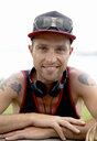 Portrait of smiling mid adult man wearing baseball cap at coast - ISF16709