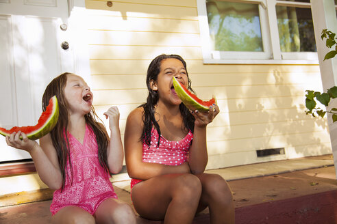 Two laughing girls sitting on house porch with slices of watermelon - ISF16763