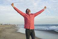 Young man celebrating on beach, Long Beach, California, USA - ISF16829