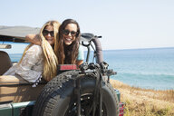 Portrait of two young women leaning out of jeep at coast, Malibu, California, USA - ISF16934