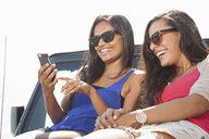 Two young women sitting on jeep hood looking at smartphone - ISF16940