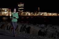 Woman running on waterfront at night - CUF39730