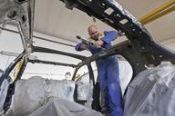 Mechanic working on car in garage - CUF39751