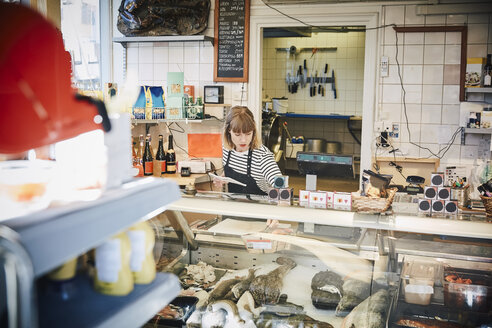 Female owner working at counter in store - MASF08018