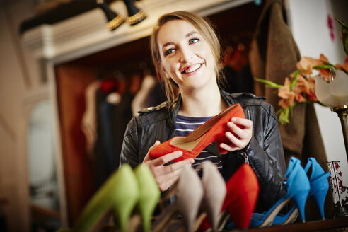 Young woman looking at selection of high heeled shoes - CUF39896