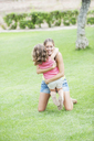 Mother and daughter hugging on lawn - CUF39923
