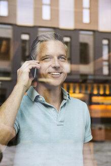 Businessmen making phone call, view through window - CUF39947