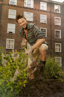 Mid adult man digging on council estate allotment - CUF39953