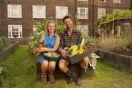 Couple holding harvested vegetables on council estate allotment - CUF39965
